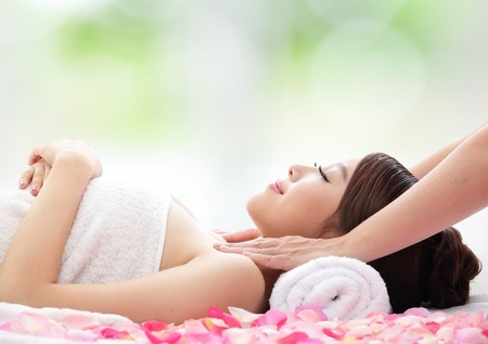 27124320 - relax beautiful woman face receiving massage with nature green background, asian beauty